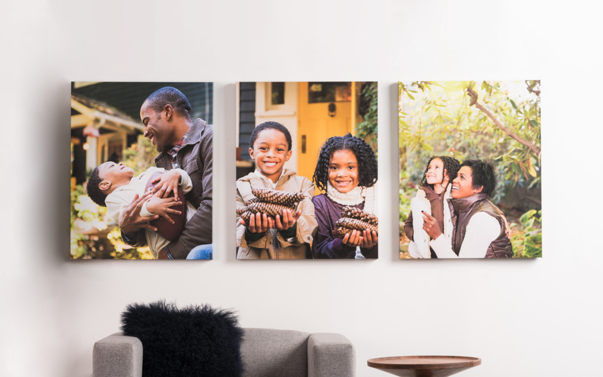 Three canvas photos of smiling family hanging on wall