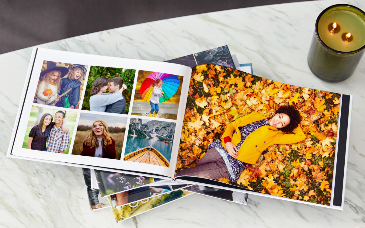 Open photo book on table with image of woman laying in fallen leaves
