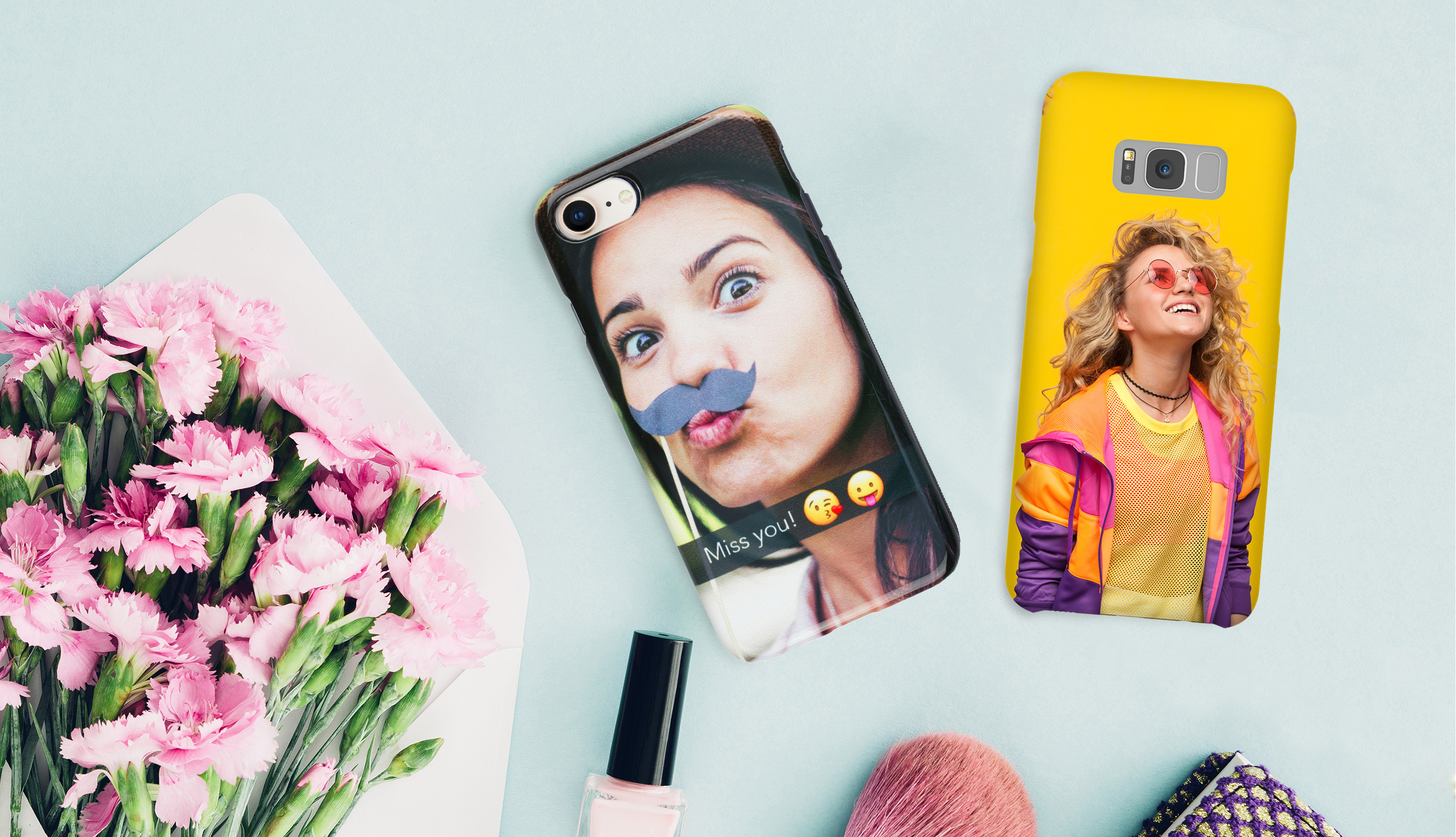 2 phone cases with selfies laying on blue tabletop