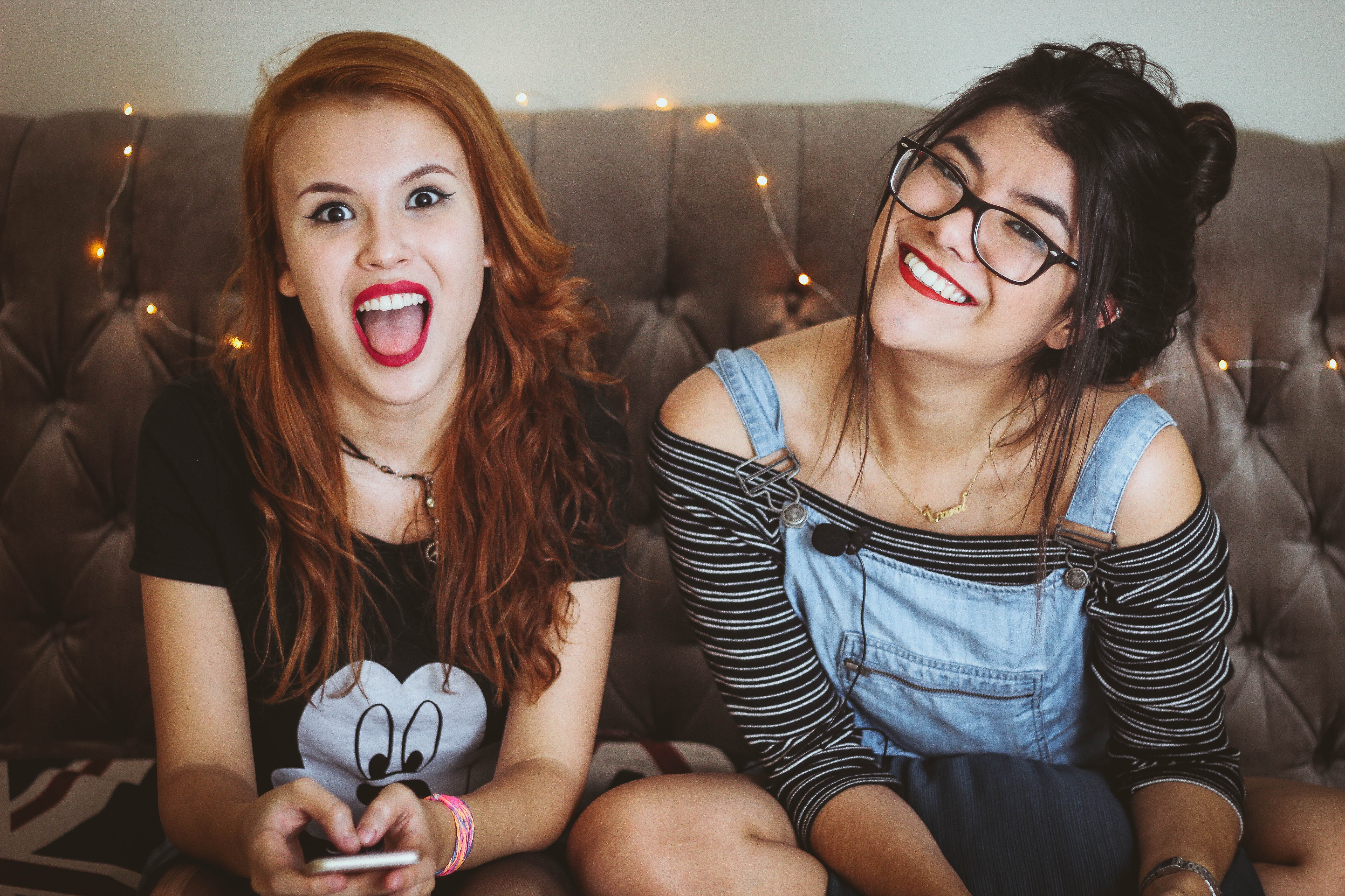 2 teenage girls sitting on couch with their smartphones
