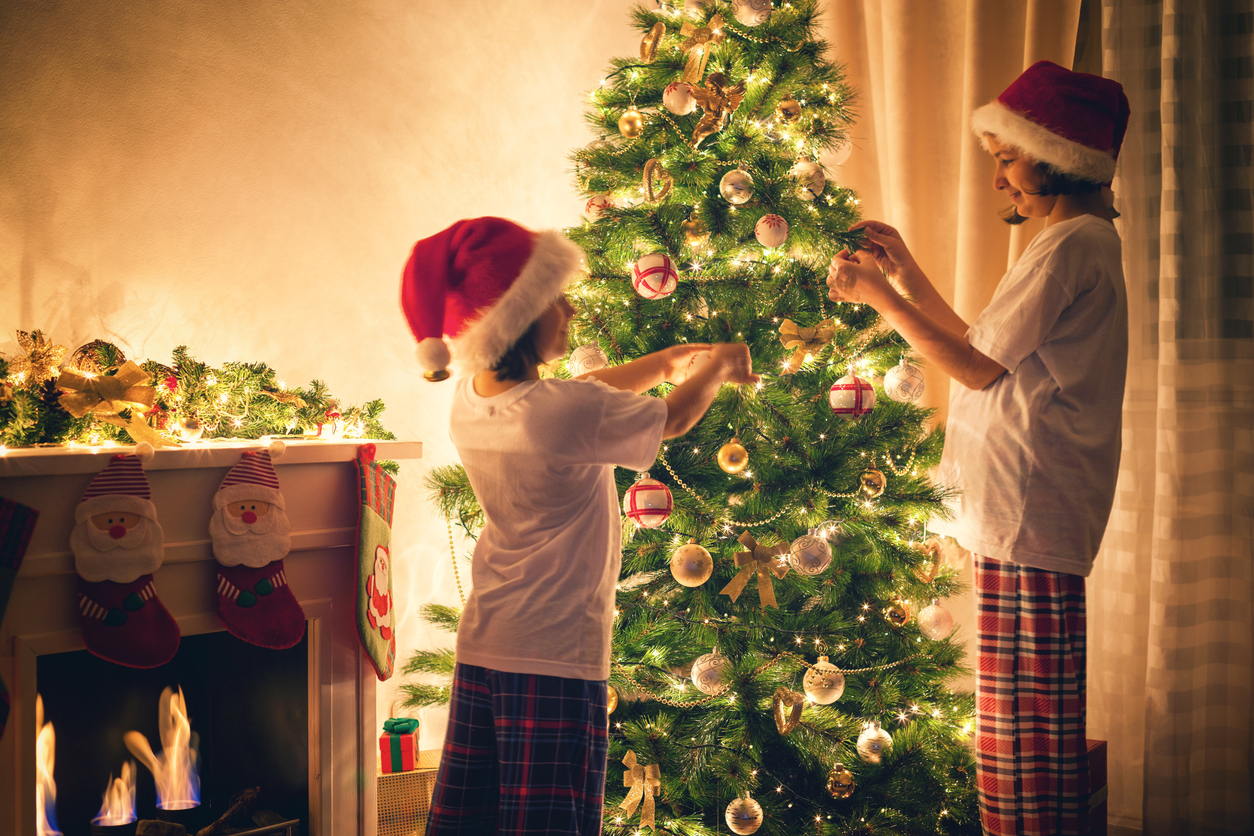Two happy sisters dressed in pajamas decorating Christmas tree together.