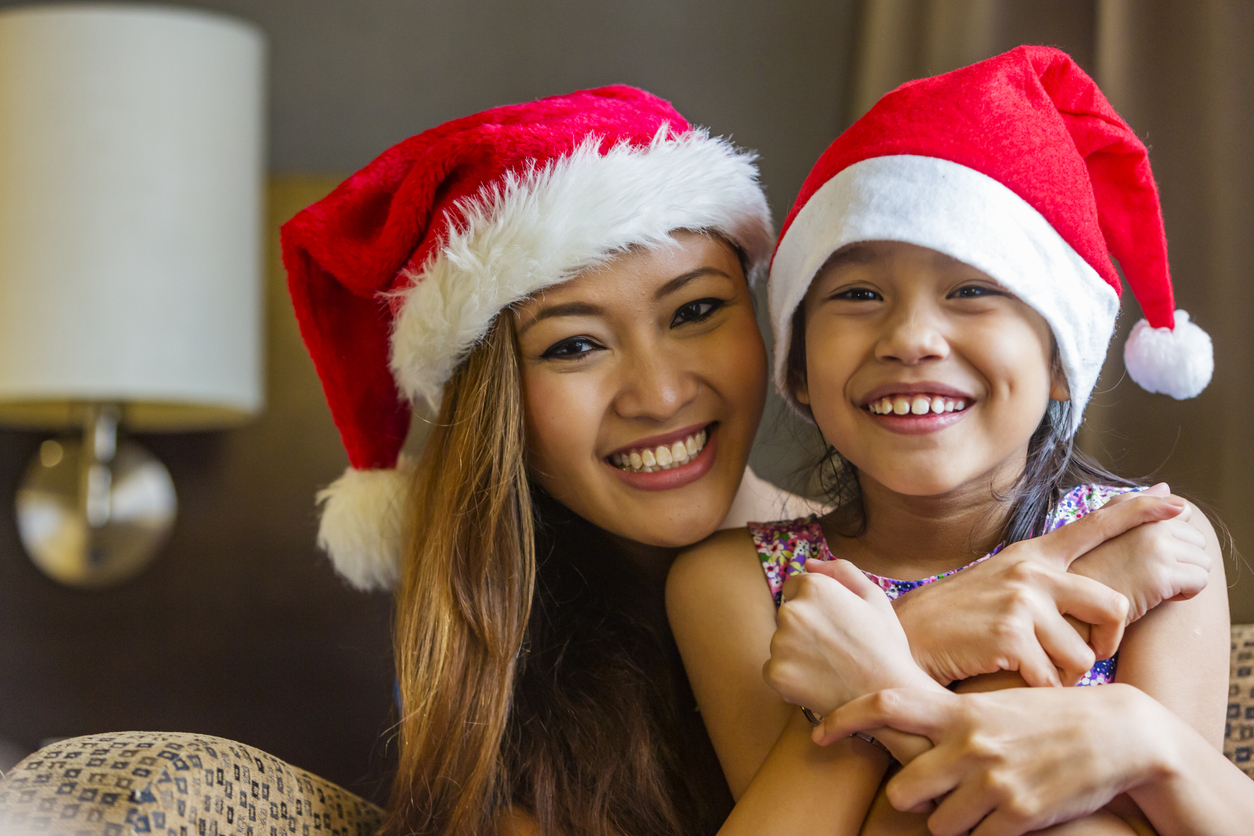 Happy Asian mother and daughter wearing Santa Claus hats