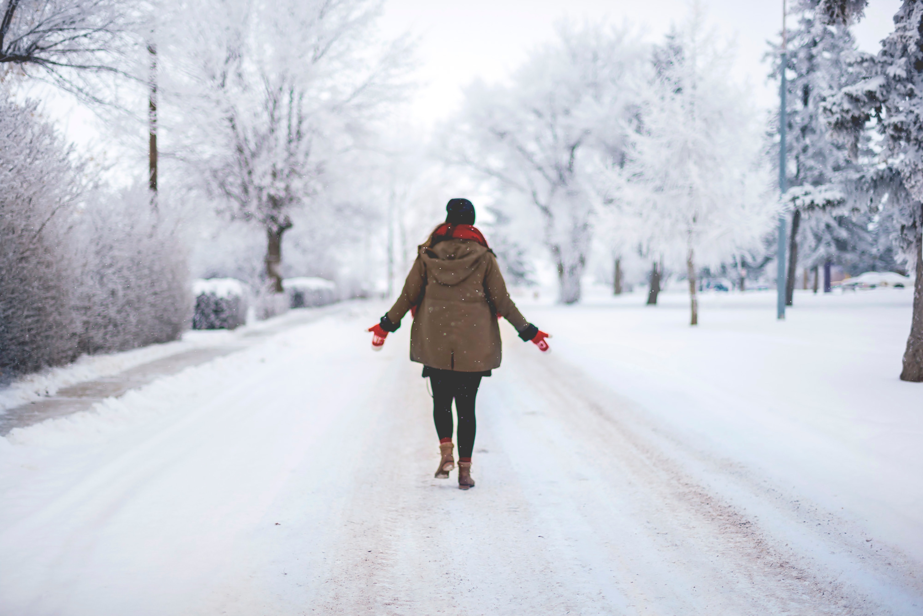 Woman walking down a snowy road